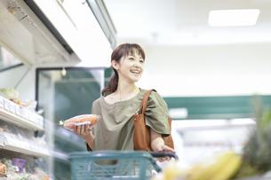 スーパーでニンジンを手に取る女性の写真素材 [FYI04948022]