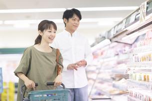 スーパーで商品を選ぶ夫婦の写真素材 [FYI04948035]
