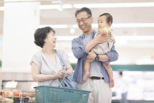 スーパーで買い物をするシニア夫婦と孫の写真素材 [FYI04948036]