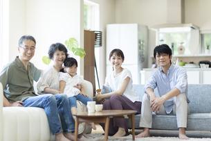 ソファーでくつろぐ三世代ファミリーの写真素材 [FYI04948041]
