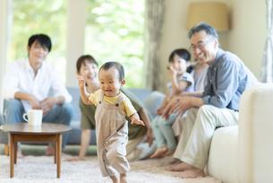 リビングで歩く子供を見守る三世代ファミリーの写真素材 [FYI04948046]