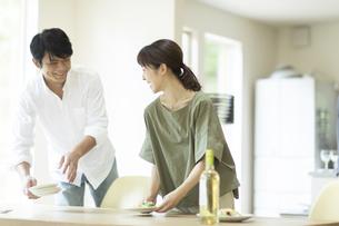 料理を運ぶ夫婦の写真素材 [FYI04948053]