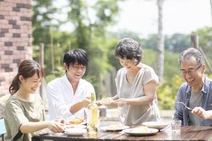 庭で食事をするファミリーの写真素材 [FYI04948060]