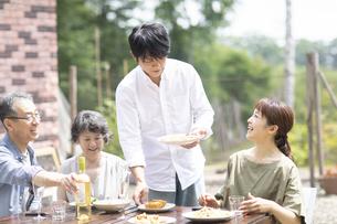 庭で食事をするファミリーの写真素材 [FYI04948062]