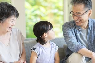 リビングで孫と話をする祖父母の写真素材 [FYI04948063]