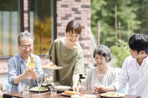 庭で食事をするファミリーの写真素材 [FYI04948064]