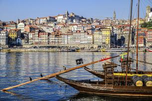 ポルトガル、川の対岸に見えるポルトの旧市街とワイン樽を運ぶ舟の写真素材 [FYI04948674]