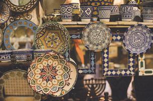 モロッコの人気観光地フェズ旧市街おみやげ屋さんに並ぶアンティークな陶器のタイルなどの写真素材 [FYI04949263]