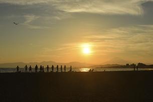 夕焼け時の富士山と相模湾の中でのビーチヨガ(シルエット)の写真素材 [FYI04949414]