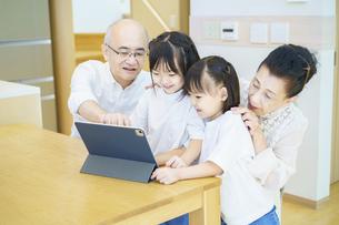 タブレットPCを操作するシニア夫婦と孫たちの写真素材 [FYI04949756]
