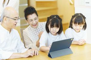 タブレットPCを操作するシニア夫婦と孫たちの写真素材 [FYI04949760]
