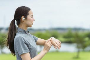 スマートウォッチを見てランニングをする女性(音声操作)の写真素材 [FYI04950405]