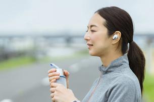 運動の途中、ドリンクを飲む女性の写真素材 [FYI04950416]