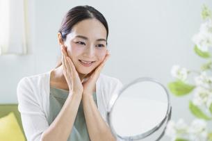 鏡を見てスキンケアをする女性(ビューティーイメージ)の写真素材 [FYI04950475]