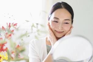 鏡を見てスキンケアをする女性(ビューティーイメージ)の写真素材 [FYI04950477]