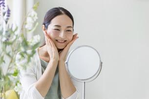 鏡を見てスキンケアをする女性(ビューティーイメージ)の写真素材 [FYI04950484]