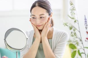 鏡を見てスキンケアをする女性(ビューティーイメージ)の写真素材 [FYI04950488]