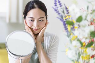 鏡を見てスキンケアをする女性(ビューティーイメージ)の写真素材 [FYI04950491]
