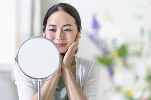 鏡を見てスキンケアをする女性(ビューティーイメージ)の写真素材 [FYI04950739]