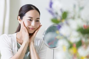 鏡を見てスキンケアをする女性(ビューティーイメージ)の写真素材 [FYI04950744]