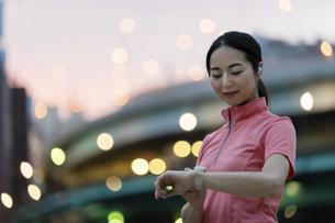 スマートウォッチを操作するスポーツウェアの女性の写真素材 [FYI04950769]