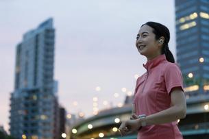 スマートウォッチを操作するスポーツウェアの女性の写真素材 [FYI04950775]