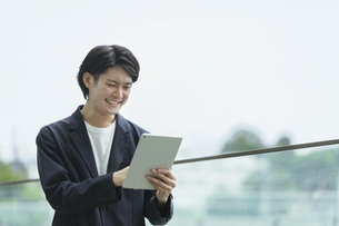 タブレットPCを操作する若い男性の写真素材 [FYI04950793]