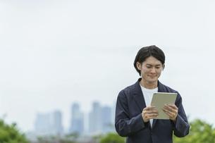 タブレットPCを操作する若い男性の写真素材 [FYI04950826]