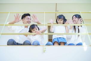 住宅の吹き抜けの上階から手を振る家族の写真素材 [FYI04951109]
