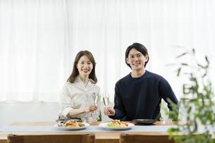 自宅でゆっくり昼食を楽しむ夫婦(ホームパーティ・おうち時間)の写真素材 [FYI04951555]
