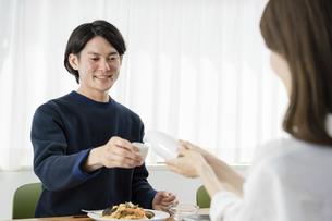 自宅でゆっくり昼食を楽しむ夫婦(ホームパーティ・おうち時間)の写真素材 [FYI04951631]