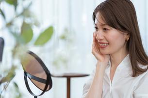 鏡を見てスキンケアをする女性(ビューティーイメージ)の写真素材 [FYI04951667]
