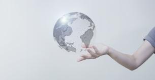 白い明るい背景と日本人女性の手と線画の地球のテクノロジーのホログラムのCGグラフィックスの写真素材 [FYI04951926]