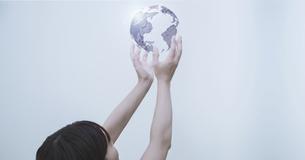 白い明るい背景と日本人女性の手と線画の地球のテクノロジーのホログラムのCGグラフィックスの写真素材 [FYI04951927]