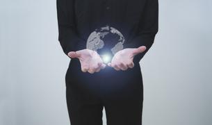 白い明るい背景と日本人女性の手と線画の地球のテクノロジーのホログラムのCGグラフィックスの写真素材 [FYI04951929]