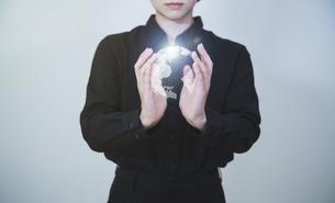白い明るい背景と日本人女性の手と線画の地球のテクノロジーのホログラムのCGグラフィックスの写真素材 [FYI04951930]