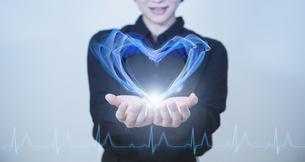 白い明るい背景と日本人女性の手とハートとヘルスケアイメージのテクノロジーのホログラムのCGグラフィックスの写真素材 [FYI04951931]