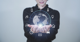 白い明るい背景と日本人女性の手と線画の地球のIOTアイコンとテクノロジーのホログラムのCGグラフィックスの写真素材 [FYI04951933]
