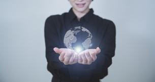 白い明るい背景と日本人女性の手と線画の地球のテクノロジーのホログラムのCGグラフィックスの写真素材 [FYI04951934]