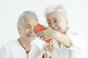 笑顔でスマートフォンの画面を見るシニア女性たちの写真素材 [FYI04952335]