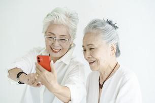 笑顔でスマートフォンの画面を見るシニア女性たちの写真素材 [FYI04952338]