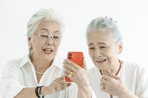 笑顔でスマートフォンの画面を見るシニア女性たちの写真素材 [FYI04952340]