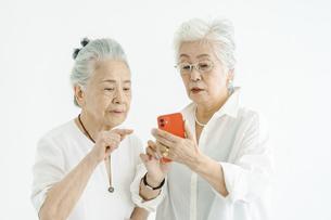 試行錯誤しながらスマートフォンを操作するシニア女性たちの写真素材 [FYI04952345]