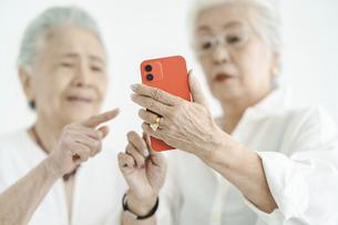試行錯誤しながらスマートフォンを操作するシニア女性たちの写真素材 [FYI04952349]