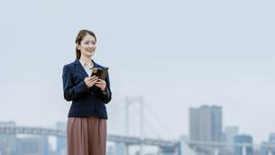 スマートフォンを持つ女性(活躍する女性のイメージ)の写真素材 [FYI04953631]
