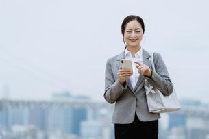 スマートフォンを持つ女性(活躍する女性のイメージ)の写真素材 [FYI04953644]