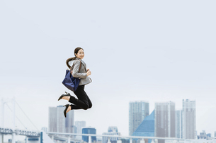 活躍する女性のイメージ(ビジネス・ジャンプ・成功)の写真素材 [FYI04953684]