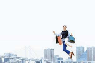 買い物袋を沢山持ってジャンプする女性(セール・爆買い)の写真素材 [FYI04953708]