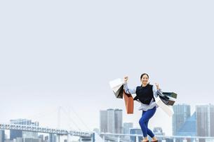 買い物袋を沢山持ってジャンプする女性(セール・爆買い)の写真素材 [FYI04953709]