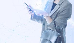 白い明るい背景と日本人女性のIOTイメージとテクノロジーのホログラムのCGグラフィックスの写真素材 [FYI04954023]